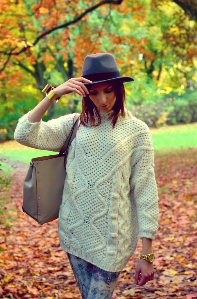 charlize mystery spaceruje jesienią w parku w niebieskim kapeluszu i białym swetrze z klasycznymi wzorami