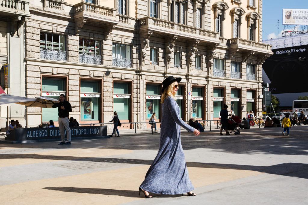 sesja modelki w kapeluszu i szarej sukience na tle kamienicy