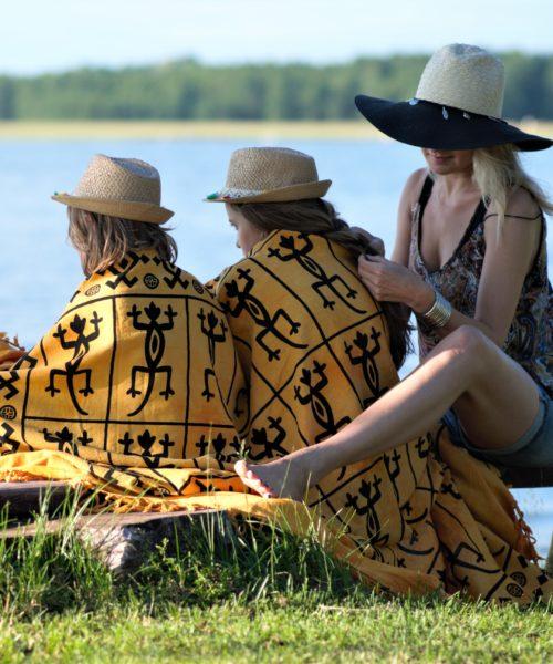 matka z córkami w kapeluszach nad wodą